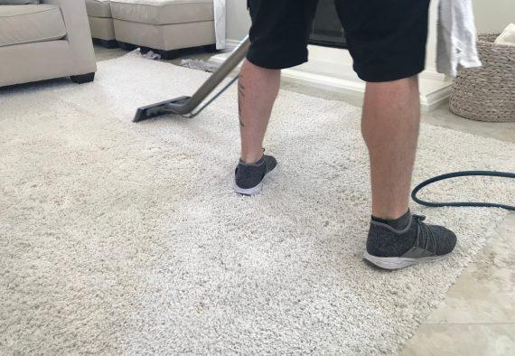 a-man-cleans-the-white-shag-carpet-at-home_t20_8d9o86
